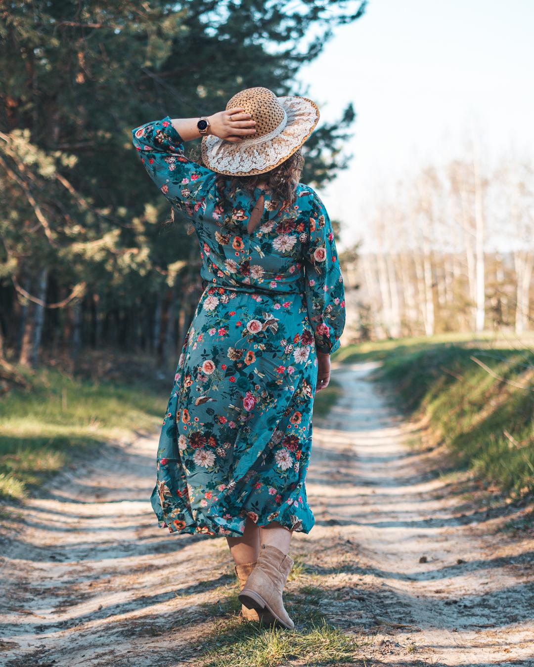 Kobieta idąca leśną ścieżką, w sukience i kapeluszu ze smartwatchem Garett na ręce