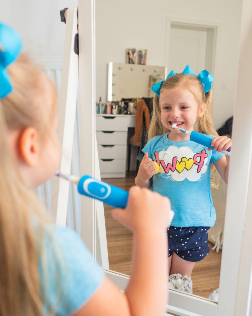 Dziewczynka szczotkuje zęby przed lustrem