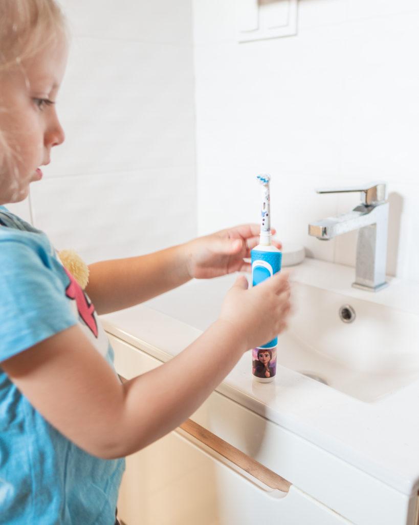 Dziewczynka ogląda elektryczną szczoteczkę do zębów