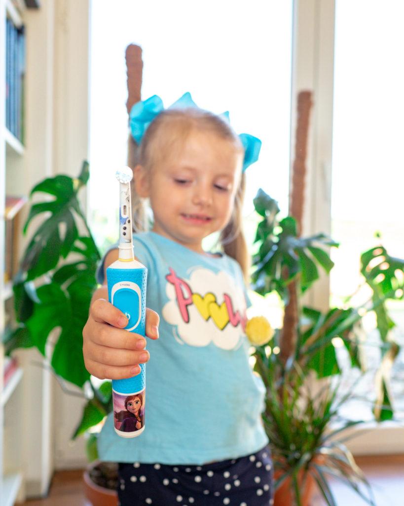 Dziewczynka pokazuje szczoteczkę elektryczną Oral-B